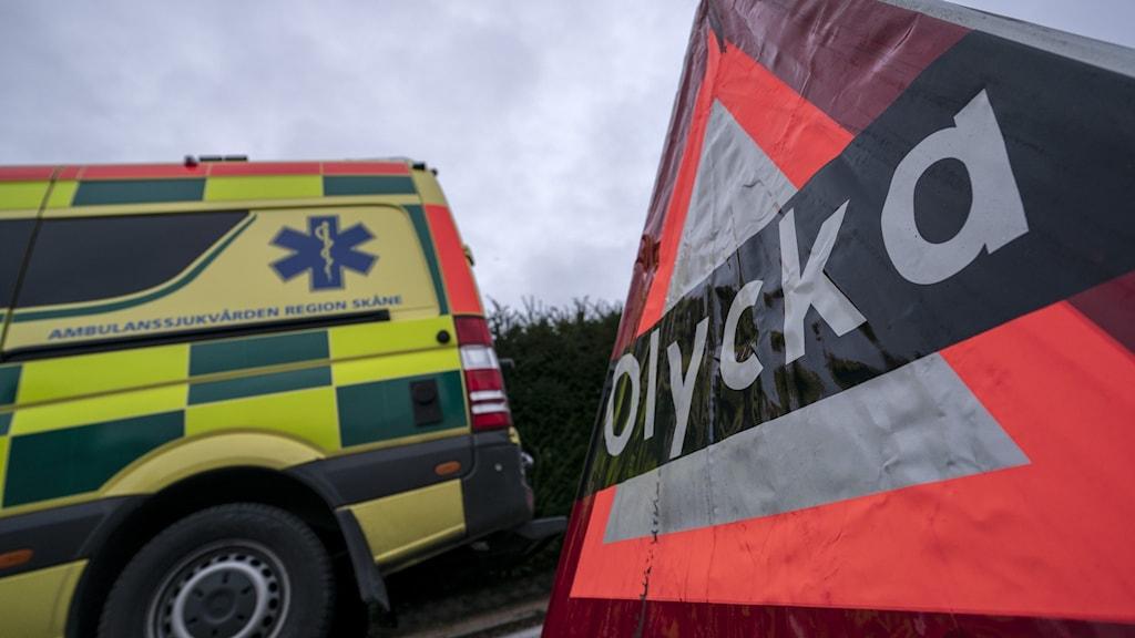 Bakdelen av en ambulans och en varningstriangel på en olycksplats.