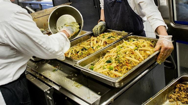två personer i skolkök heller upp mat i lådor av metall