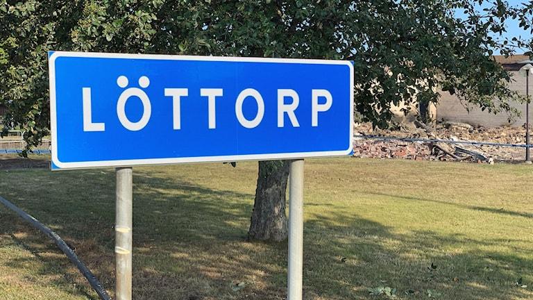 Löttorp, skylt, med Åkerboskolans brandplats i bakgrunden.