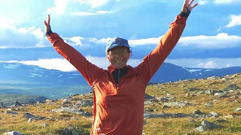 Pia SJöholm står på ett fjäll iklädd orange jacka med armarna upp i luften.