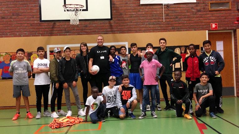 """Shemsi """"Papi"""" Brahimi tillsammans med ett gäng ungdomar i en sporthall."""