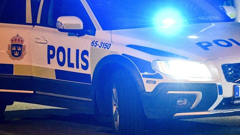 Parkerad polisbil med blåljus påslagna.
