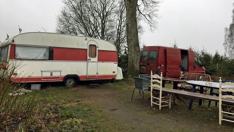 Husvagn och skåpbil på gården där de som tvingats tigga bott.