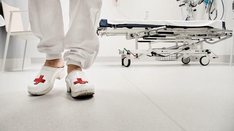 Fötterna på sjukvårdspersonal som har träskor med röda kors på.