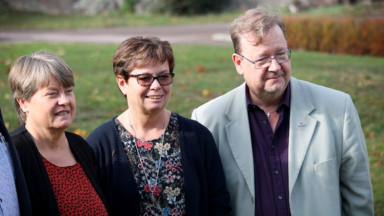 Två kvinnor och en man som står utomhus.