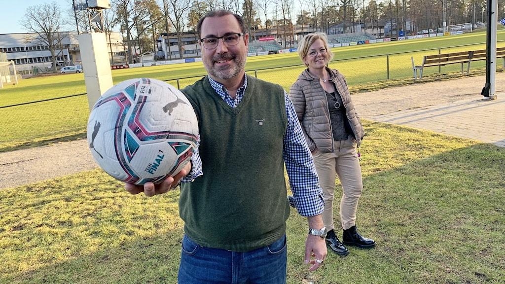 Två personer står på en gräsmatta. En person håller i en boll.
