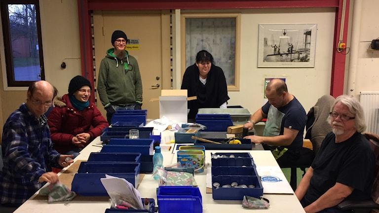 Arbetsdeltagare som bearbetar ljushållare.