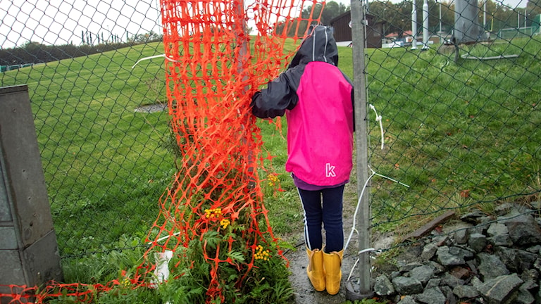 Flicka står på idrottsplats med regnjacka och stövlar. Hon tittar innanför något rött när.