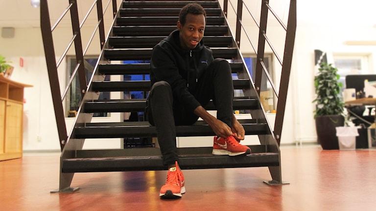 Omar Mahamed Ismail sitter i en trapp med löparskor på.
