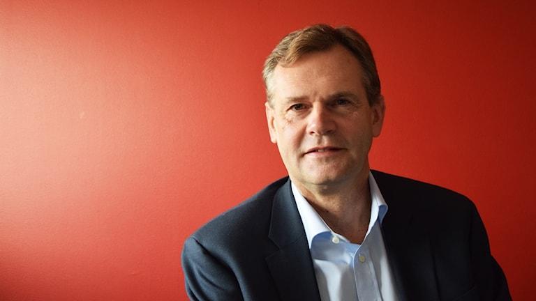 Johan Assarsson framför en röd vägg.