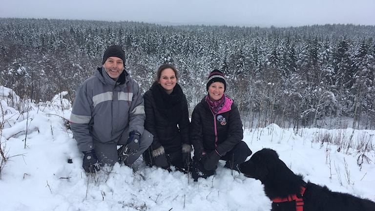 Personer med hund framför snötäckt skog.