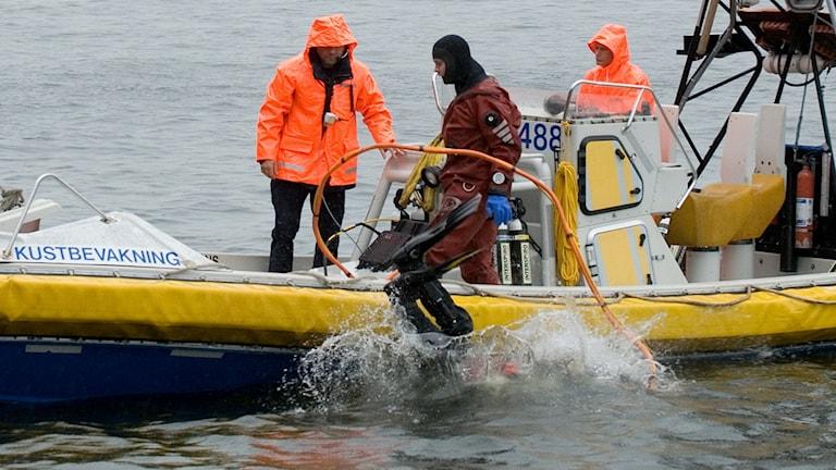 Dykare från kustbevakningen som hoppar i vattnet från en mindre båt.