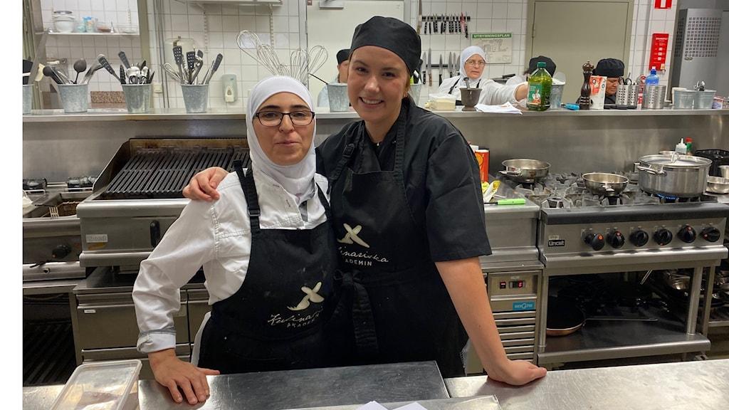 Två glada tjejer i köket på restaurangutbildningen tittar in i kameran