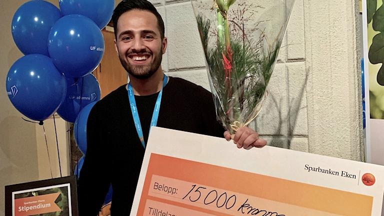 Azad Ali med stipendiet på 15 000 kronor, ballonger och blommor.