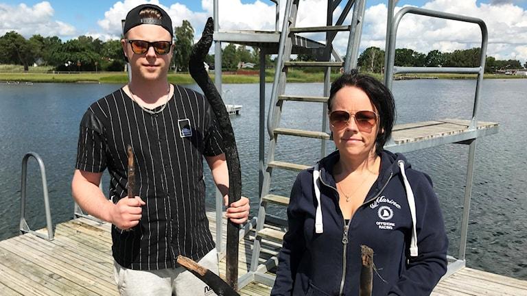 Två persoenr står på en brygga framför ett hopptorn. En person håller i en spetsig pinne.