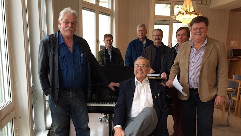 Medlemmar i Ölands manskör ståendes runt en flygel