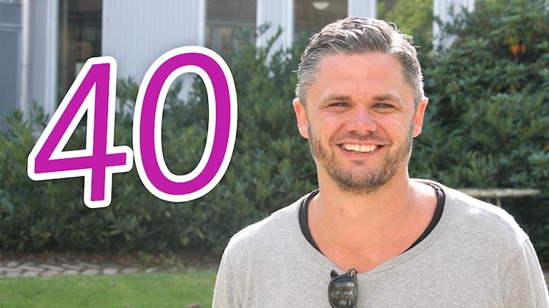 Svante Ekberg står utomhus med siffran 40 bredvid sig