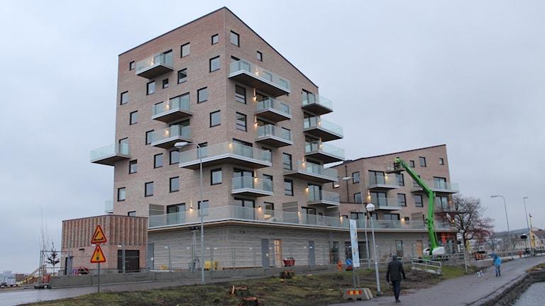 Nya Slottsholmen med balkonger och tegelfasad i förgrunden en grön lyftkran och en man passerar framför huset.