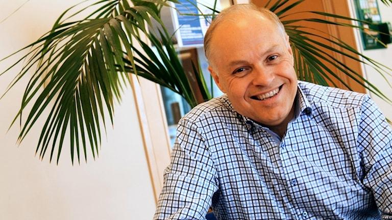 Thomas Carlzon i skjorta framför växt.