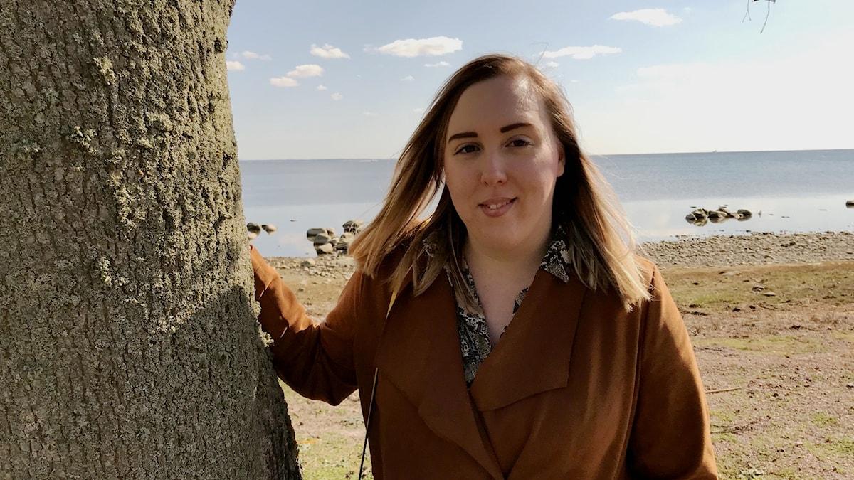 Studenten Lilly Olofsson vid ett träd