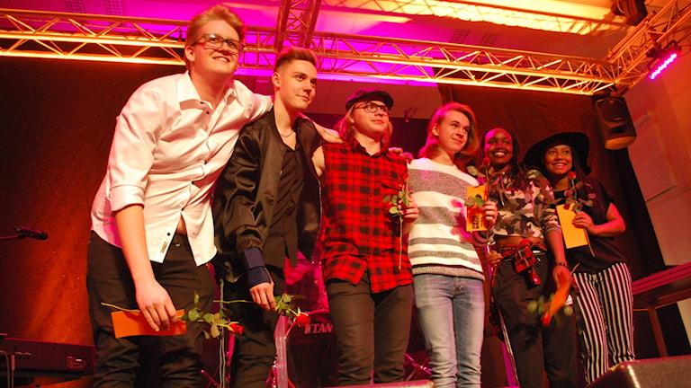 Sex personer på en scen.