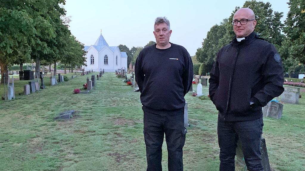 Två personer står på en kyrkogård.