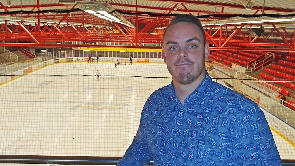 En man i blå skjorta står framför en tom hockeyis.