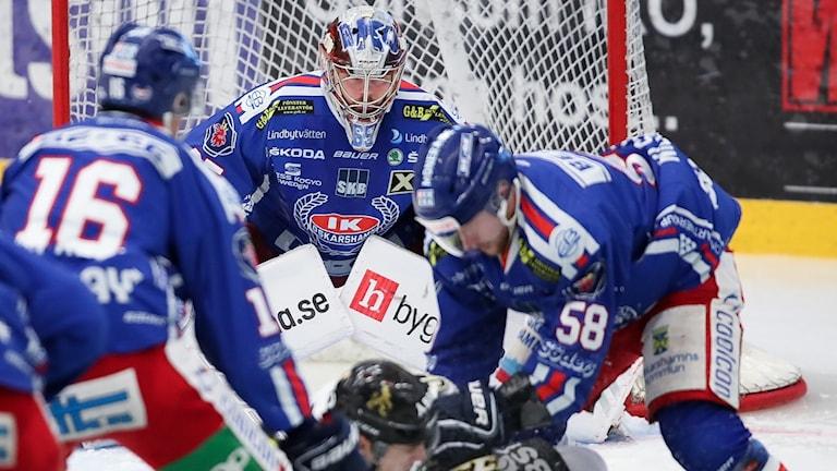 En ishockeymatch med bild på målvakten i fokus.