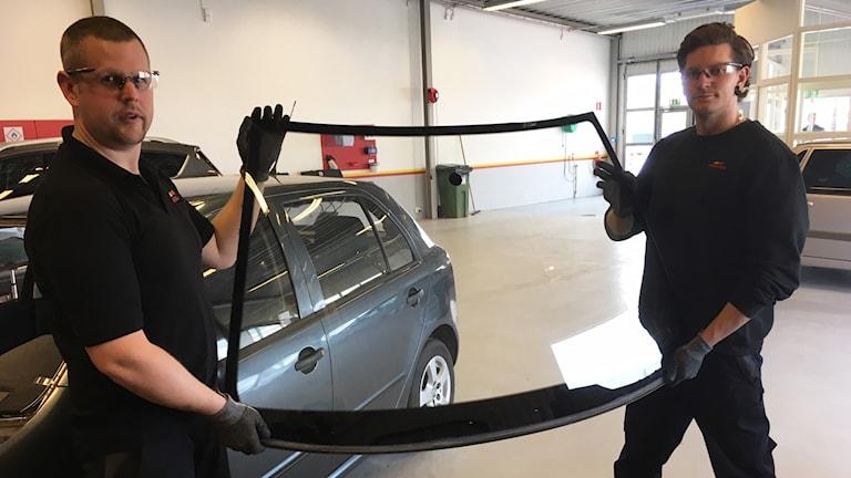 Michel Svensson och Daniel Truedsson håller upp en framruta till en bil.