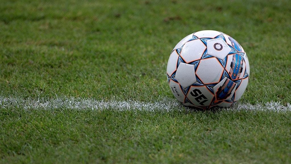 En fotboll som ligger på en fotbollsplan.