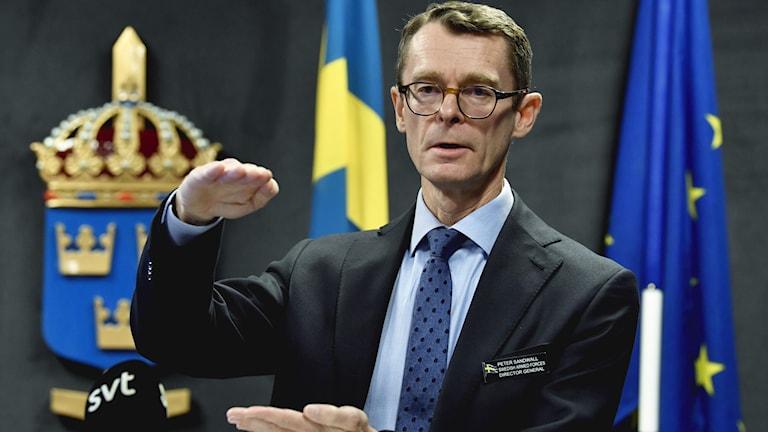 En person står framför svenska flaggan.