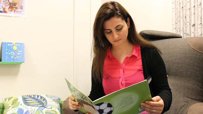 Kulturvärd Roya Saydomimi läser bok på arabiska.