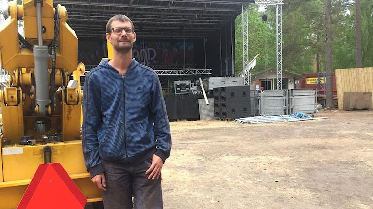 Johan Grusell står framför bygget av stora scenen och tittar in i kameran.