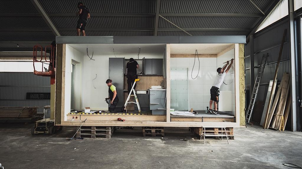 Två män bygger en modul till hus av trä