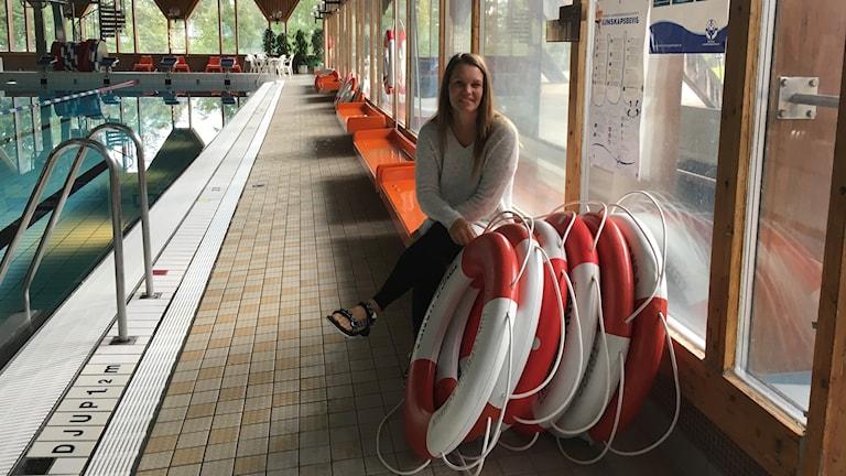 Maria Bohlin sitter intill en simbassäng.