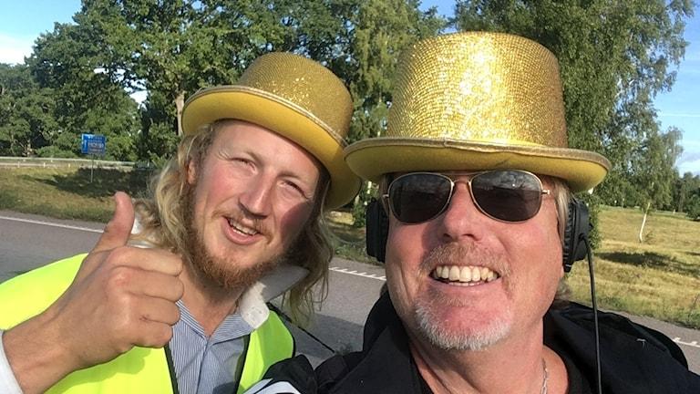 Liftare Mathias och reporter Peter i gula silvriga hattar
