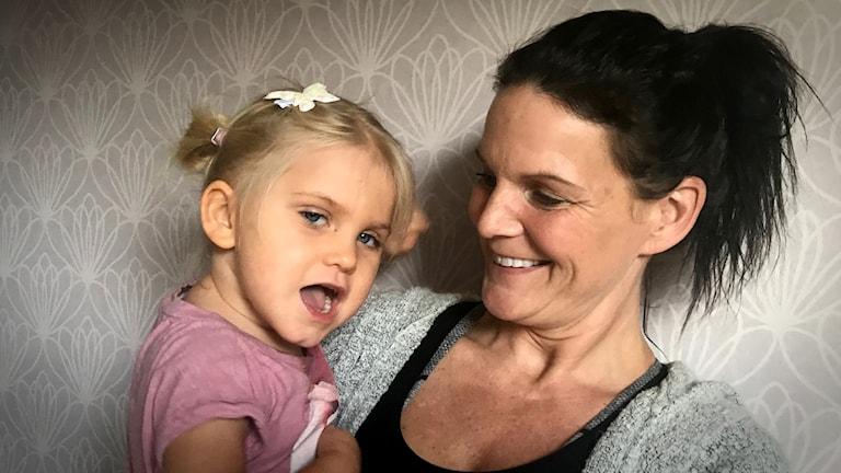 En mamma med en liten flicka i famnen