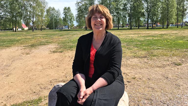 En kvinna som sitter på en stor sten med gräs och träd i bakgrunden.