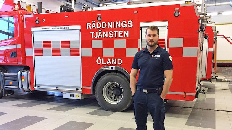Rutger Thuresson, brandman på Öland, framför en brandbil.