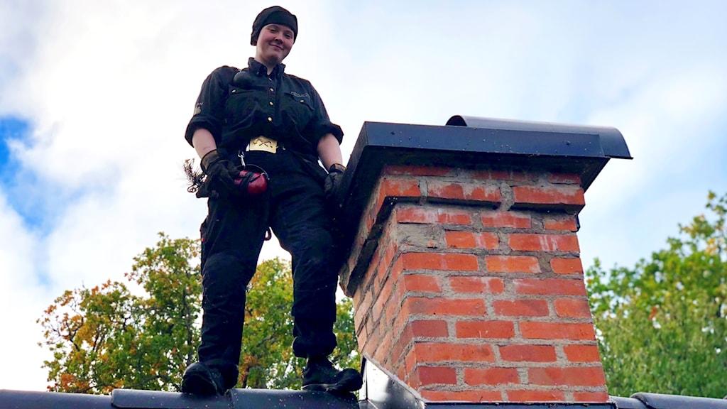 Kvinnlig sotare uppe på ett tak