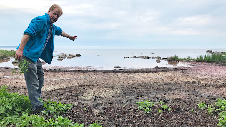 En man som pekar på strandavfall.