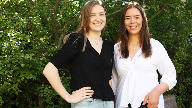 Två kvinnor poserar framför en grön buske.