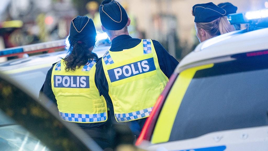 Flera poliser står samlade vid uppställda polisbilar.