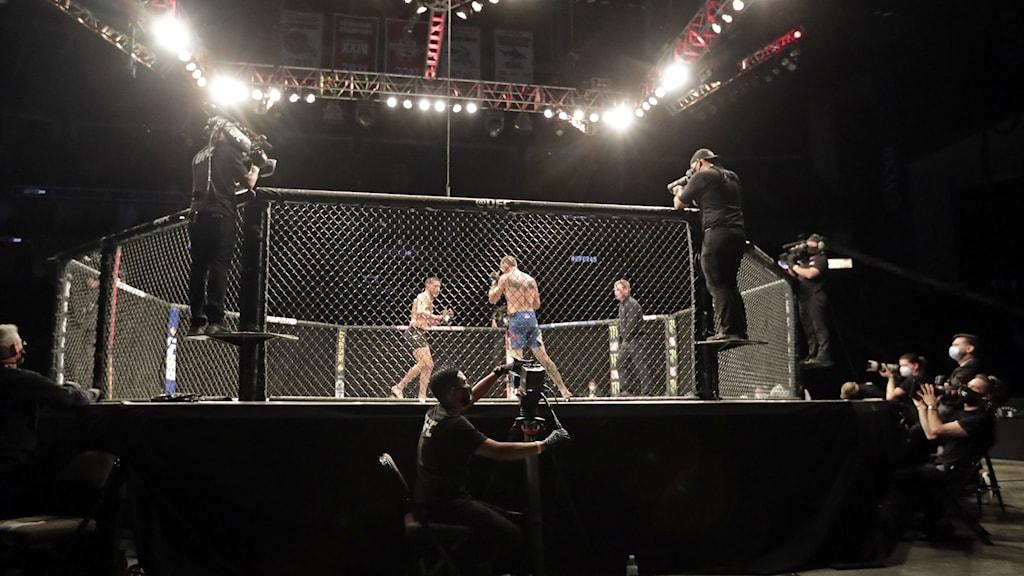 En oktagon där två kampsportare möts i MMA.