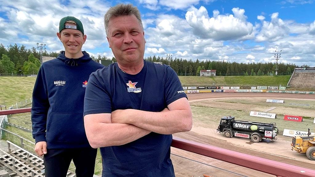 Två personer står på en balkong, i bakgrunden ser man en speedwayarena.