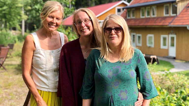 Tre kvinnor framför en byggnad