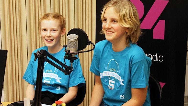 Två personer sitter i en radiostudio med Vi i femman-tröjor på sig.