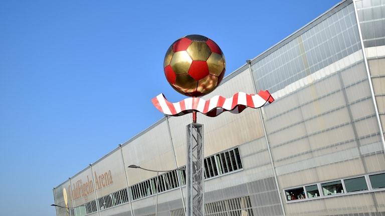 Fotboll i rött och guld på en pelare utanför en fotbollsarena.