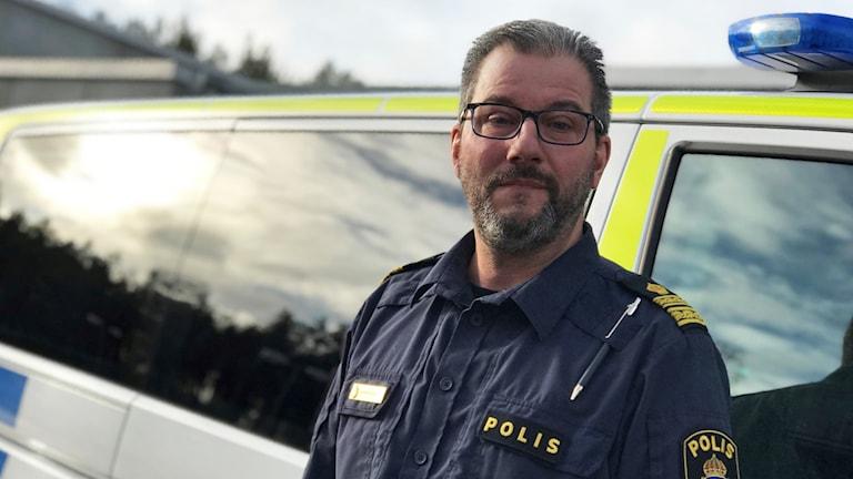 Anders Pleijel står vid en polisbil.