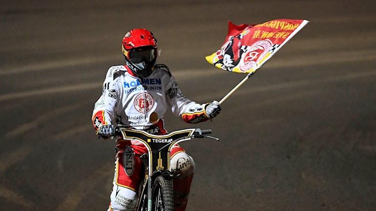 Speedwayförare med flagga.
